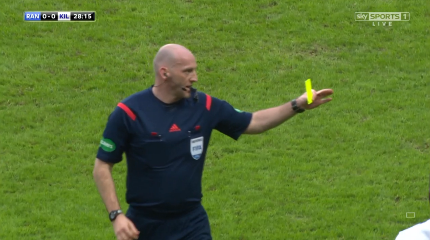 Referee Bobby Madden issues a yellow card