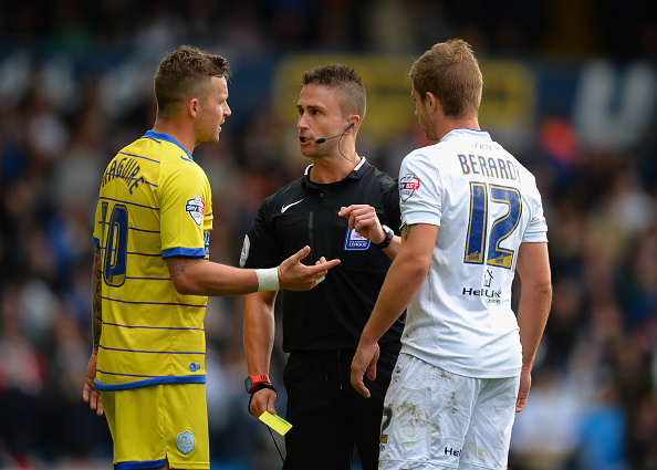 LEEDS, ENGLAND - OCTOBER 04: Referee James Adcock talks to Gaetano Berardi of Leeds United and Chris Maguire of Sheffield Wednesday before giving both players a yellow card during the Sky Bet Championship match between Leeds United and Sheffield Wednesday at Elland Road on October 4, 2014 in Leeds, England. (Photo by Tony Marshall/Getty Images)